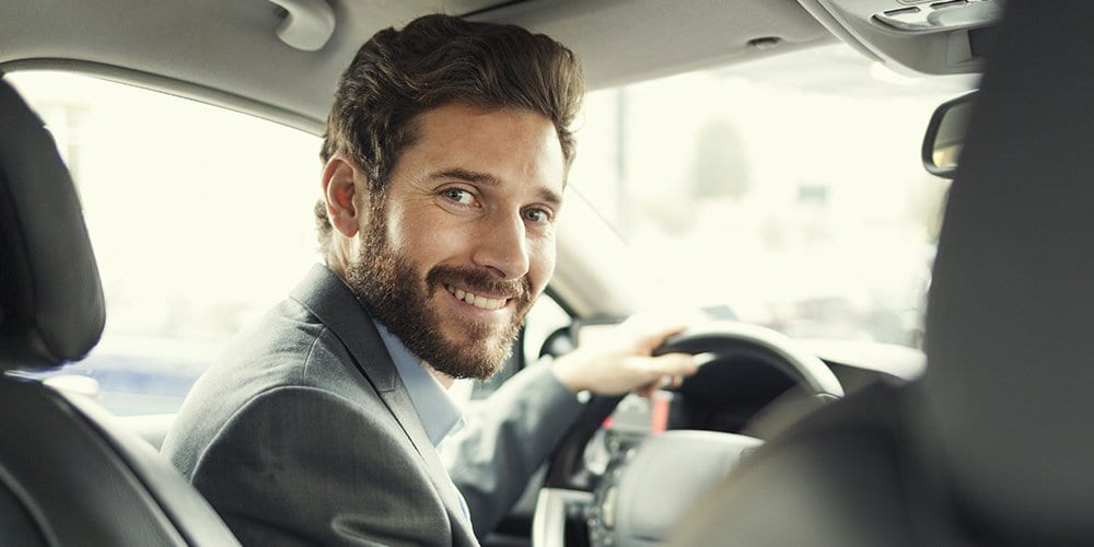 man smiling behind the wheel of a car