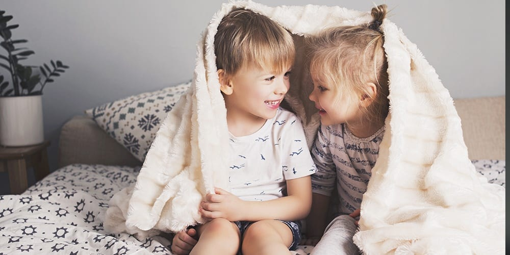 child siblings smiling and wrapped in a blanket