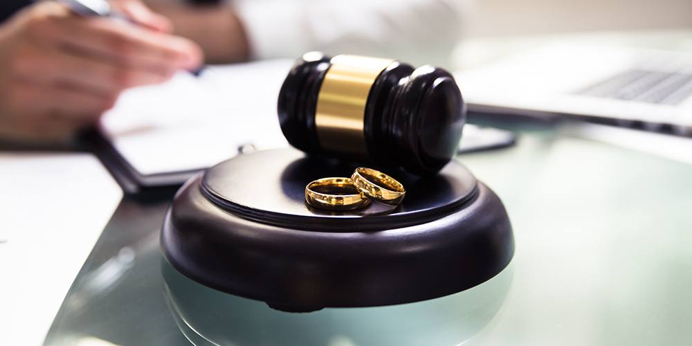 two gold wedding rings on a table next to a gavel