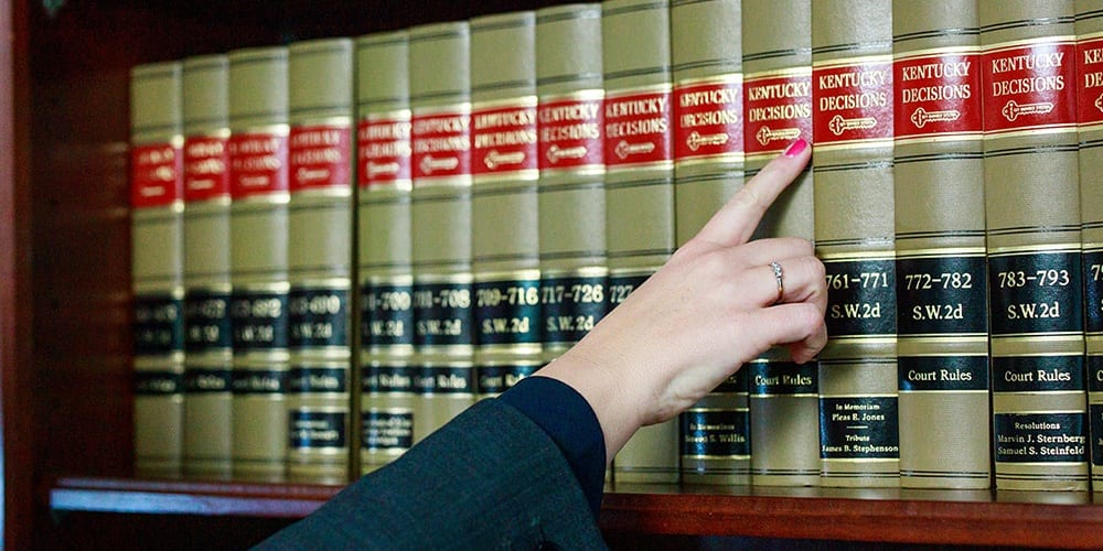 hand pointing to a book on a bookshelf