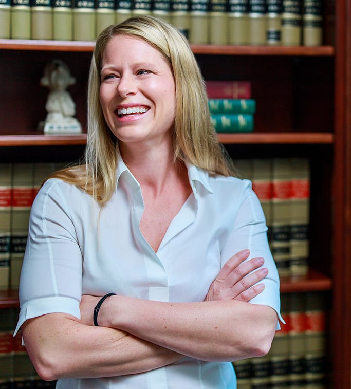 Attorney Cassie Clagget Crossing Arms and Laughing in her Office