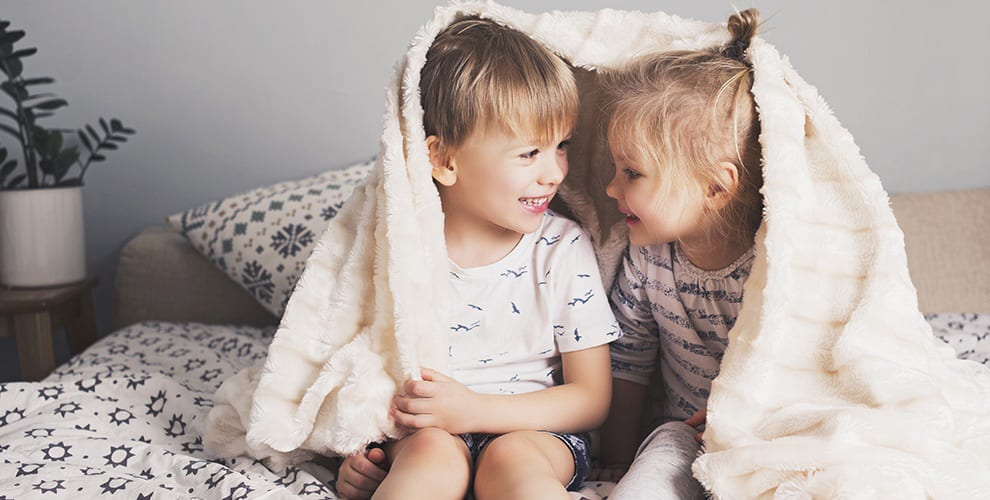 Two Caucasian Child Siblings Wrapped in Blanket on Bed