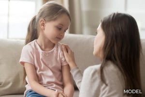Loving mom talking to upset little girl at home on couch