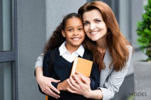 Happy Mother Hugging Adoptive Daughter Before School
