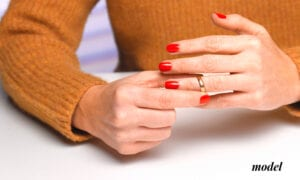 Close Up of Female Hands Removing Wedding Ring