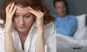 Upset Female Holding Head at Top of the Bed with Husband Behind Her