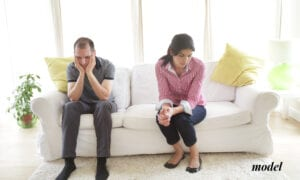 Upset Married Couple Sitting Apart From Each Other on the Couch